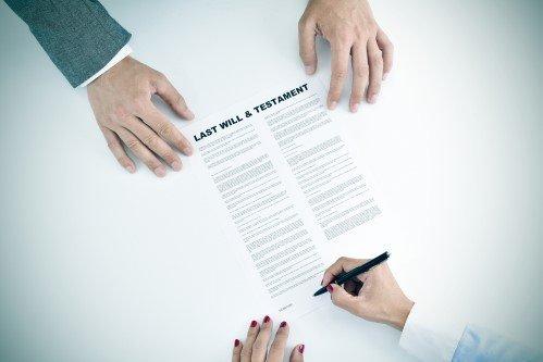 אשה חותמת על צוואה בפני עורך דין