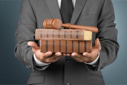 עורך דין מחזיק ספרי חוק ופטיש של בית משפט