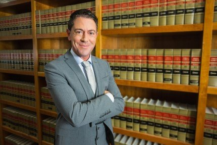 עורך דין עומד ליד ספריה של ספרי משפט