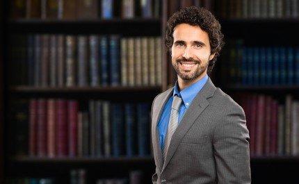 עורך דין עומד לפני ספרייה מלאה בספרי חוק