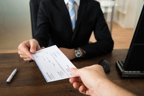 אדם מגיש צ'ק של תשלום לפקידה של ביטוח לאומי